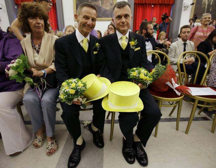 Angelo Albanesi, left, and Pier Giorgio De Simone wait for their civil union to be registered by a municipality officer during a ceremony in Rome's Campidoglio Capitol Hill.