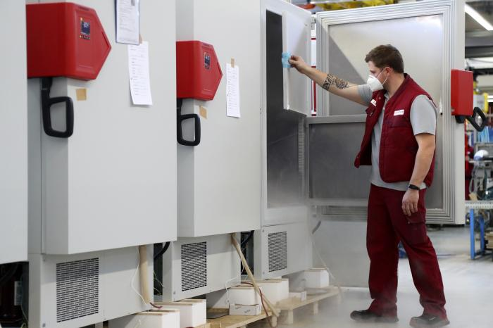 In this Tuesday, Nov. 24, 2020 file photo an employee of Binder, the world's largest manufacturer of serial-production environmental simulation chambers for scientific or industrial laboratories, checks an ultra low temperature freezer in Tuttlingen, Germany.