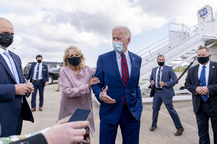 Jill Biden moves her husband, Democratic presidential candidate former Vice President Joe Biden, back from members of the media as he speaks outside his campaign plane at New Castle Airport in New Castle, Del.