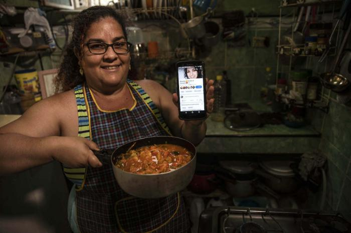 """Contributor Yuliet Colon poses for a photo holding a pot of her creation, """"Cuban-style pisto manchego,"""" and her phone that displays the Facebook page, """"Recipes from the Heart."""""""