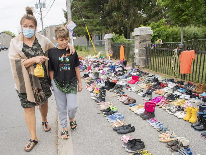Lynn Karonhia-Beauvais and grandson Jamieson Kane walk past shoes representing the remains of 215 children outside St. Francis Xavier Church in Kahnawake, Quebec, Sunday, May 30, 2021.