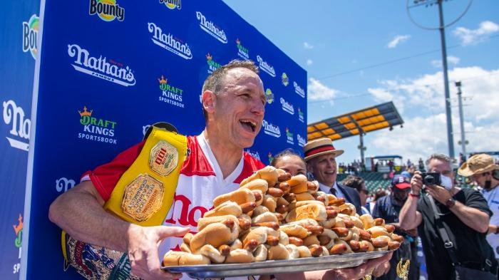 Winners Joey Chestnut and Michelle Lesco, obscured behind hot dogs, pose at the Nathan's Famous Fourth of July International Hot Dog-Eating Contest in Coney Island's Maimonides Park on Sunday, July 4, 2021, in the Brooklyn borough of New York. (AP Photo/Brittainy Newman)
