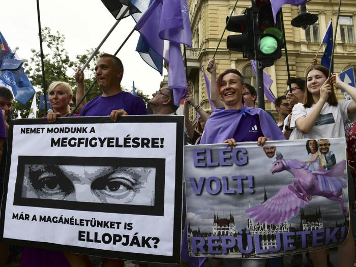 """People hold banners show Hungarian Prime Minister Viktor Orban, reading: """"We have to say no for observation!'' and ''Do they already stole our private life?"""", left, and """"It was enough! Fly!"""" during a protest against the government's alleged use of powerful spyware to spy on opponents, Budapest, Hungary, July 26, 2021."""