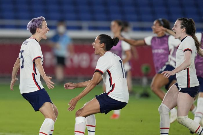 United States' Megan Rapinoe, left, celebrates with teammates after scoring the winning goal and defeating the Netherlands in a penalty shootout during a women's quarterfinal soccer match at the 2020 Summer Olympics, Friday, July 30, 2021, in Yokohama, Japan. (AP Photo/Silvia Izquierdo)